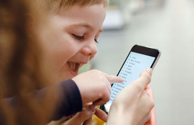 Lapsi katsoo älypuhelinta, joka on aikuisen kädessä.