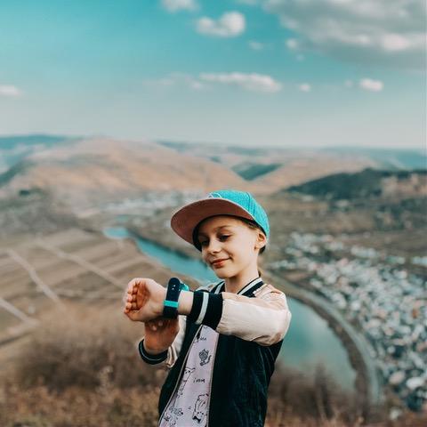 Lapsi katsoo xplora puhelintaan. Taustalla aukeaa maisema vuoristoon.