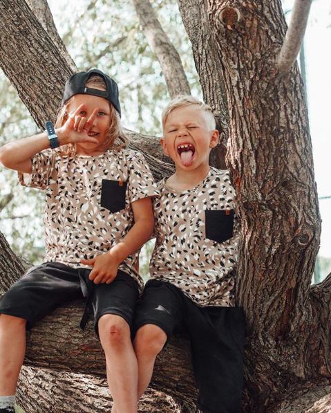 Veljekset istuvat puussa ja ilmeilevät leikkisästi.