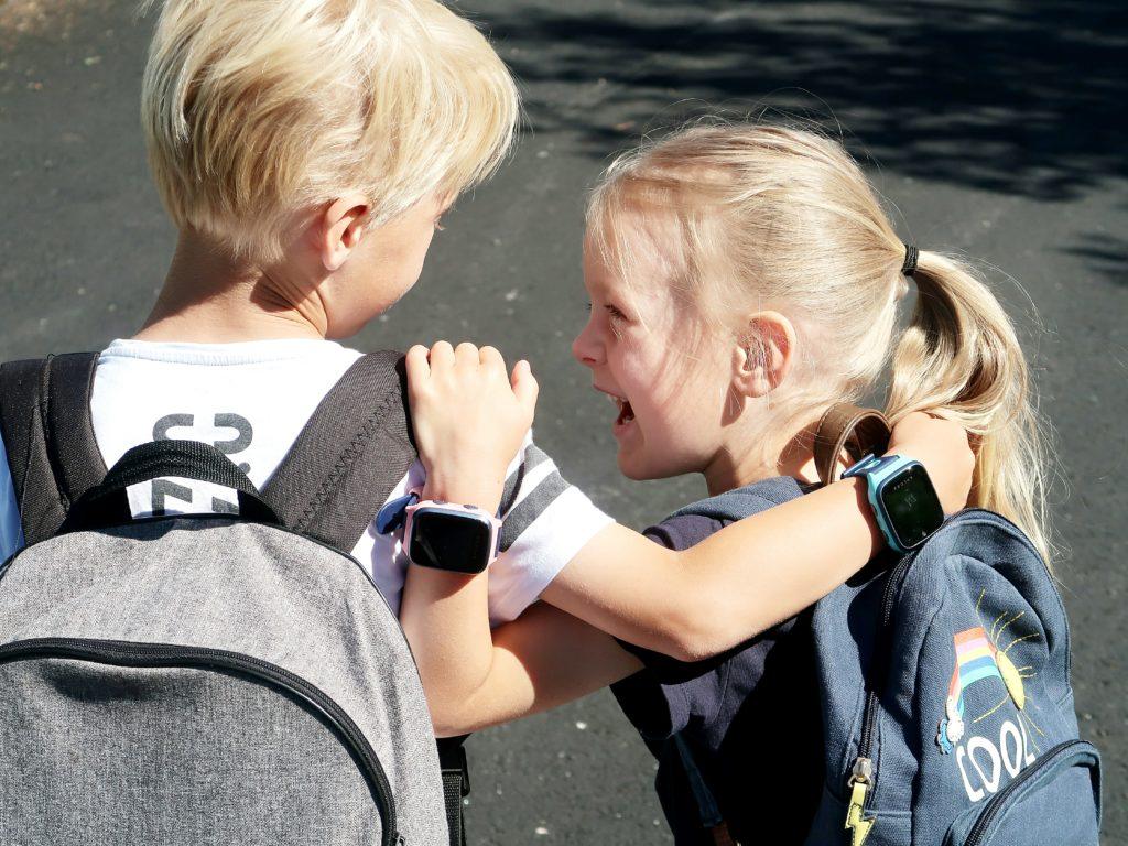 Koululaiset iloisina Xplora ensipuhelimet ranteissaan ja reput selässä