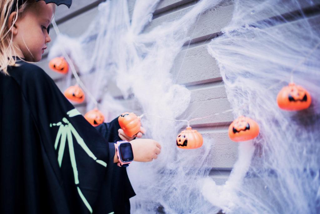 tyttö pukeutuneena halloween asuun sekä pieniä kurpitsavaloja