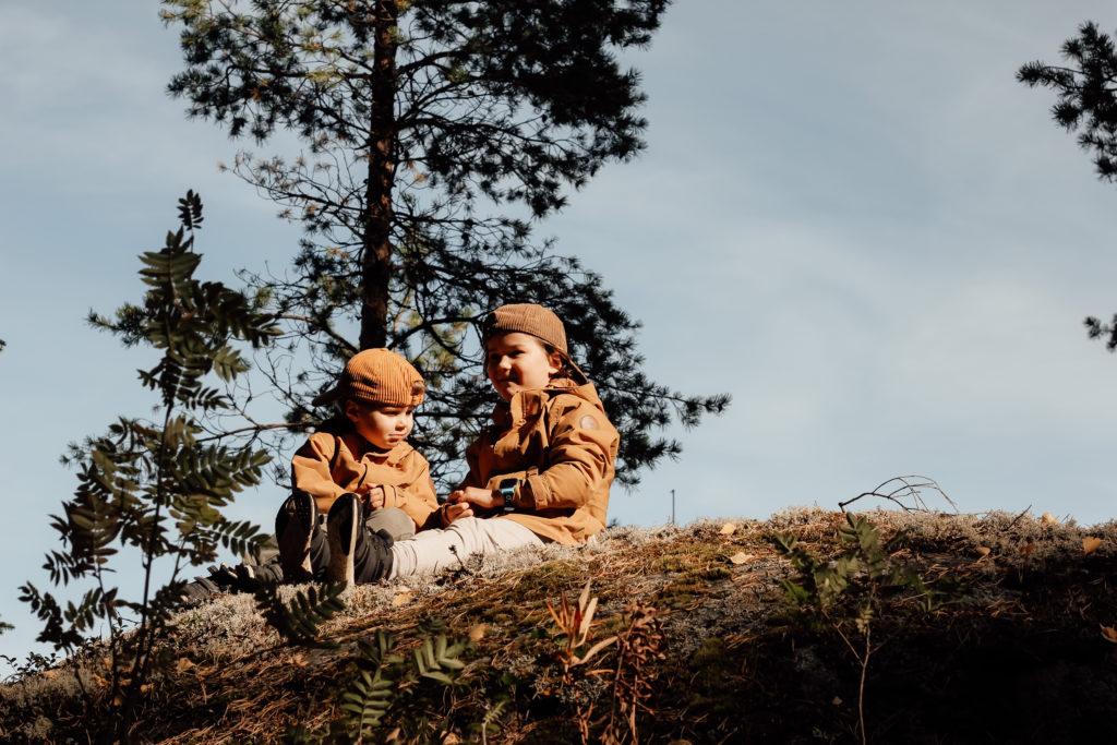 Lapset istuvat kalliolla.