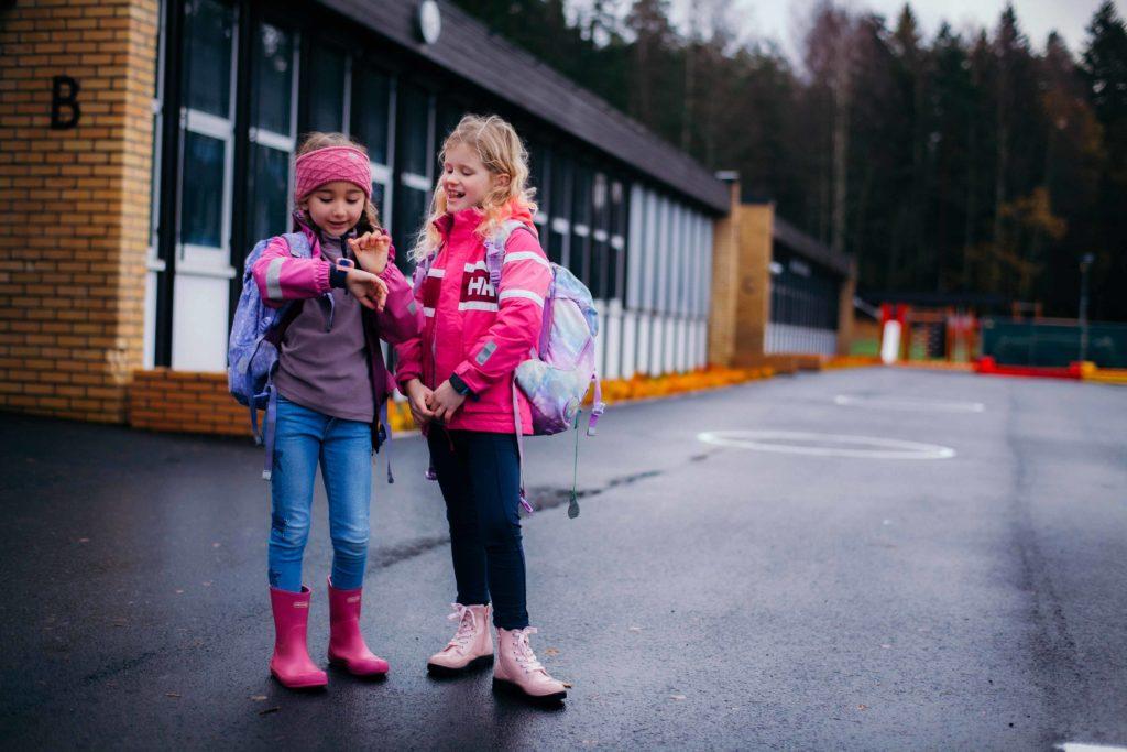 Xplora lapsen ranteessa koulunpihalla. Puhelin koulusssa.