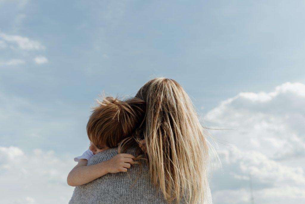 Lapsi äidin sylissä. Lasten GPS tuot turvaa.