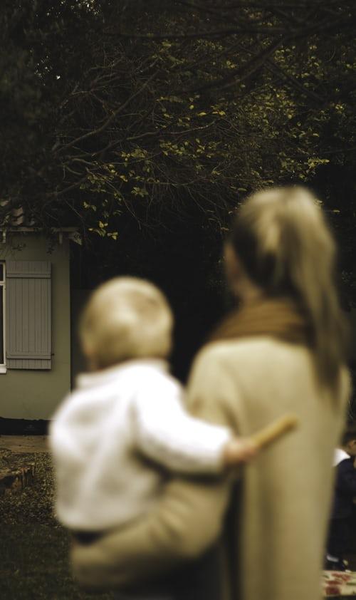 Äiti seisoo ulkona lapsi sylissään.