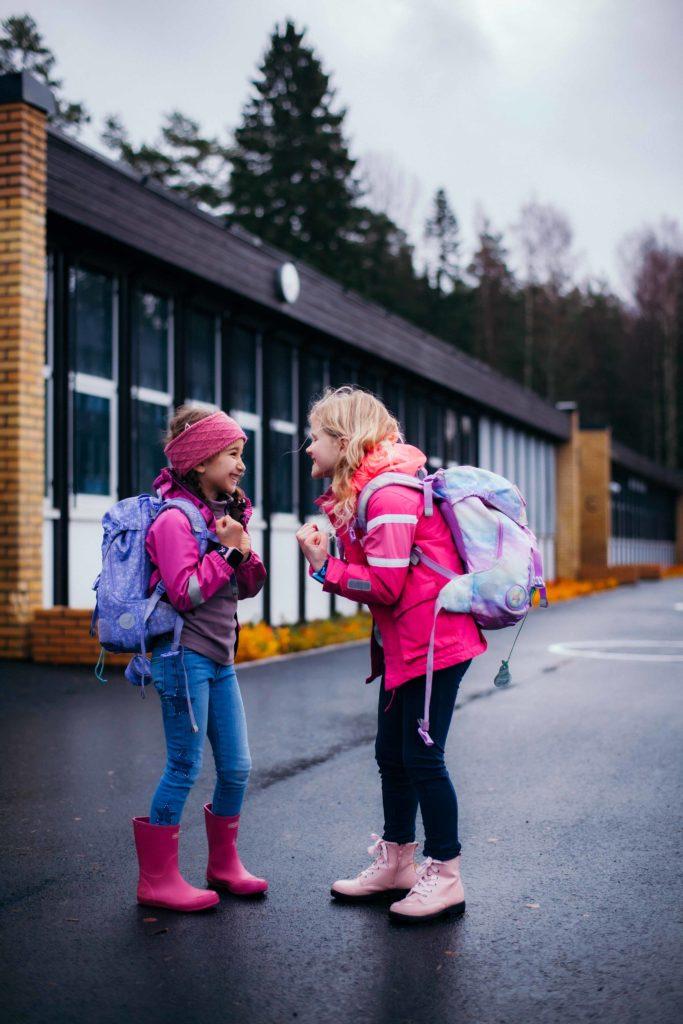 Lasten ensimmäinen puhelin. Koululaiset pihalla Xplora puhelin ranteessa.