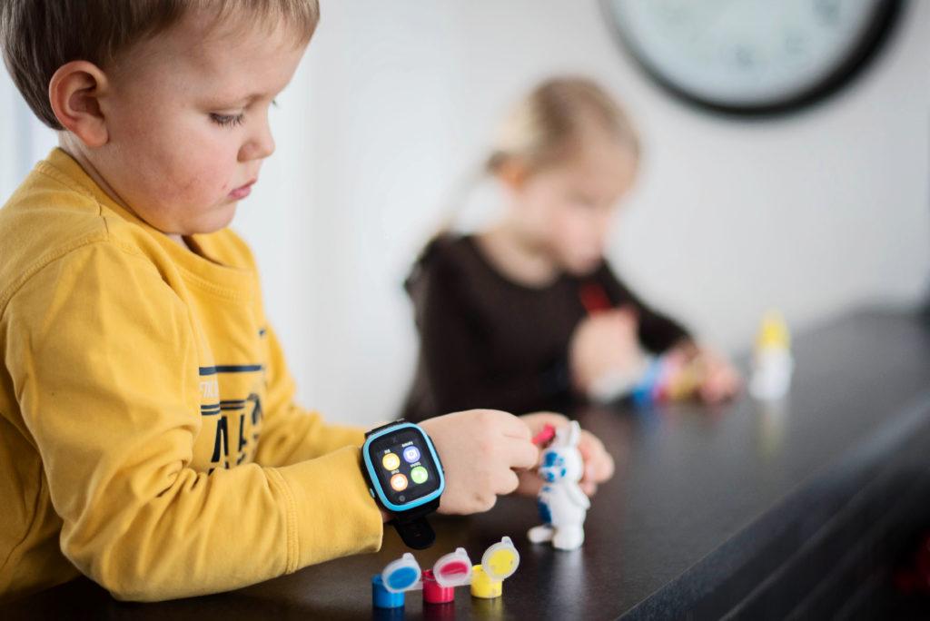Lapsi maalaa keskittyneesti. Xplora 5 puhelin on lapsen ranteessa.
