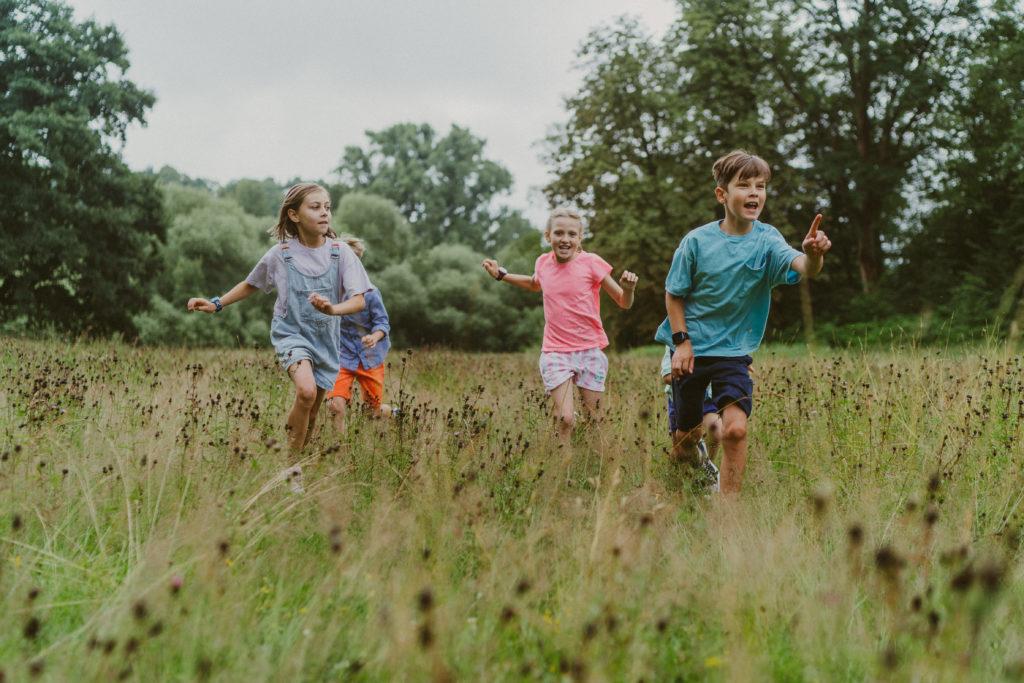 Lapset juoksevat niityllä