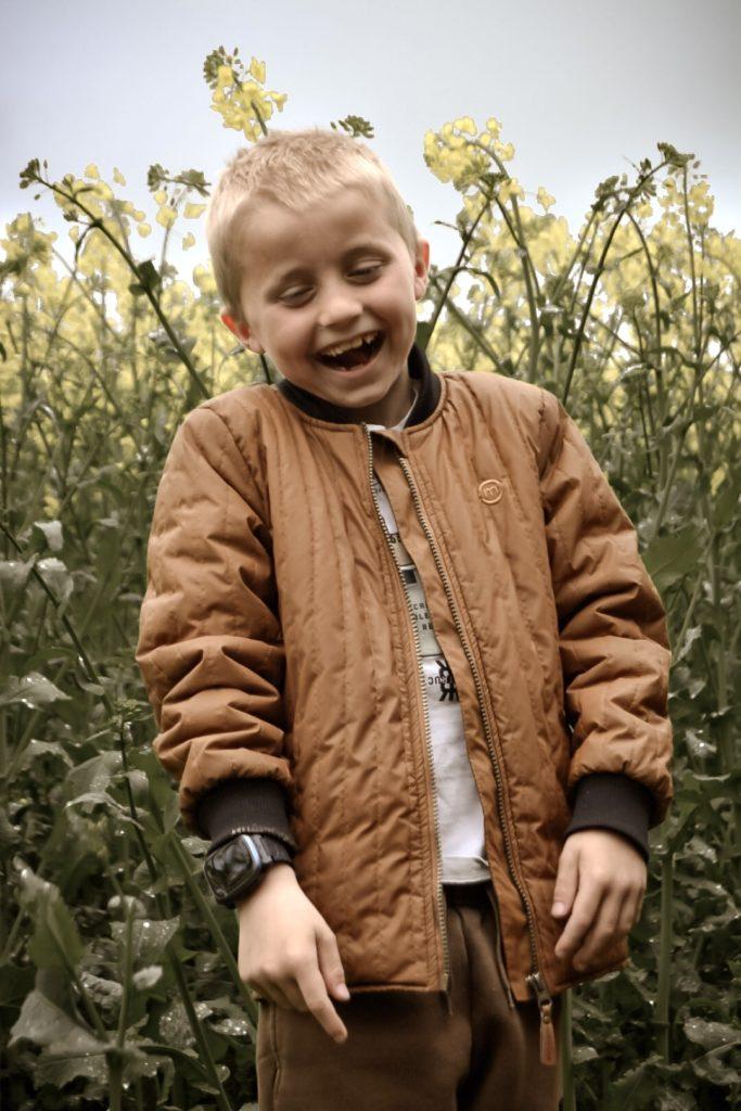 Lapsi seisoo niityllä ja nauraa. Xplora X5 Play ranteessa.