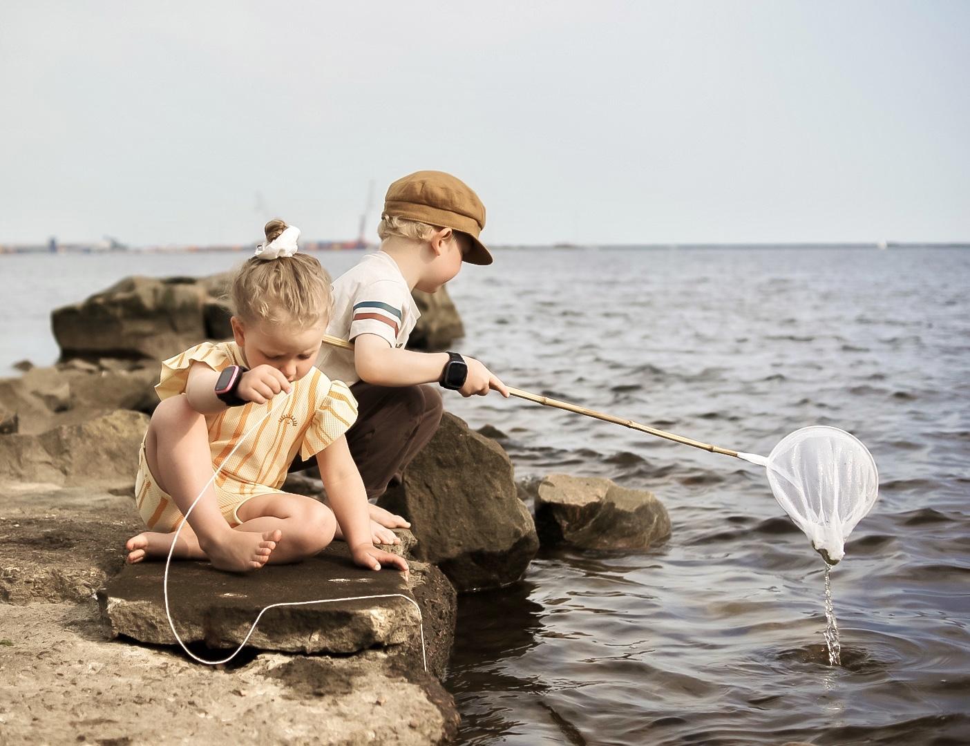 Lapset kalassa Lasten kellopuhelin ranteessa.