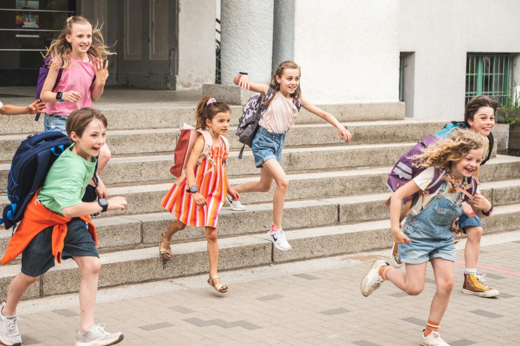 Lapset juoksevat koulun portaita alas.